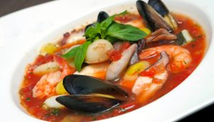 Tomato soup with seafood and fish in a plate